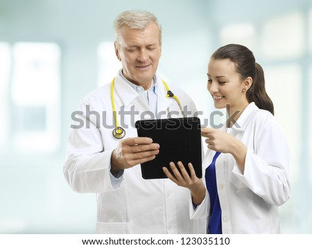 Senior doctor and her assistant standing in the hospital, watching his digital tablet, and discussing reports