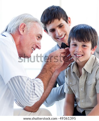 Senior doctor examining a little boy's ears at the practice - stock photo