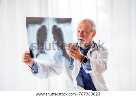 Senior doctor looking at chest x-ray in office. #767960023