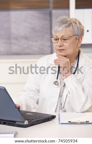 Senior doctor looking at computer screen, thinking.?