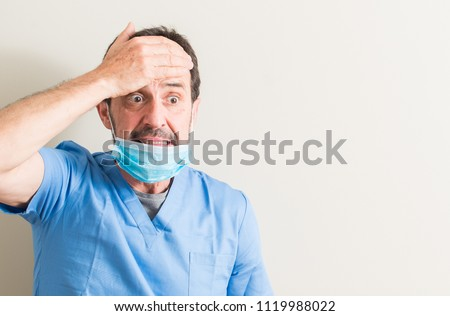 Senior doctor man using mask stressed with hand on head, shocked with shame and surprise face, angry and frustrated. Fear and upset for mistake.
