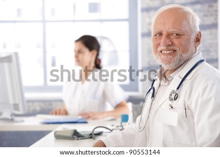 Senior doctor sitting at desk in office, smiling, looking at camera