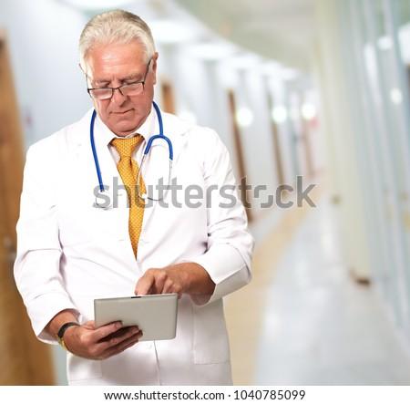 Senior Doctor Using Digital Tablet, Indoors