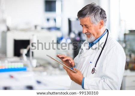 Senior doctor using his tablet computer at work color toned image