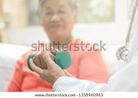 Senior elderly Asia woman with medical caregiver or physical therapist helping patient holding dumbbell in physical therapy session. Healthy old people concept.