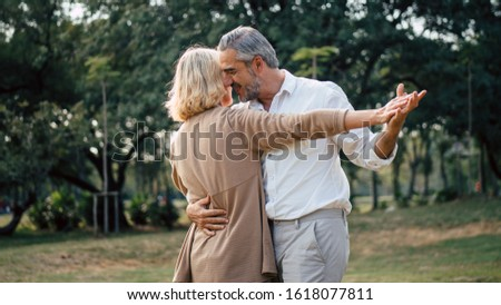Senior elegant caucasian couple dancing looking at each other feeling love and cherish on their anniversary in the park with copy space, happily retired spouse, well-managed retirement life concept.