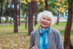 senior elegant stylish fashionable woman in coat outdoor in autumn park. Anti age, old age, seasons, fall concept