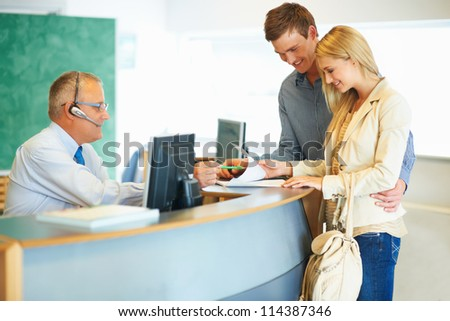 stock photo : Senior employee handing a couple the contract for their car rental so they can sign it