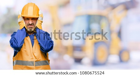 Photo of  Senior engineer man, construction worker covering ears ignoring annoying loud noise, plugs ears to avoid hearing sound. Noisy music is a problem. at work