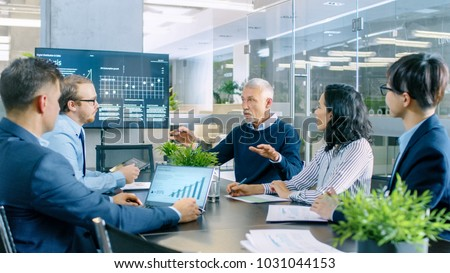 Senior Executive Explains Company's Vision and Potential to His Employees. They are Sitting at Big Table in Meeting Room. TV Screen on the Wall Shows Corporate Growth.