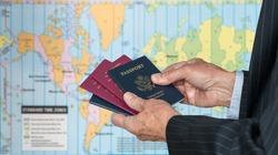 Senior executive hand holding USA and UK passports against blurred background of world map of timezones