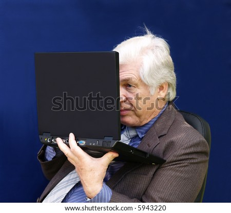 Senior executive  looking closely at his laptop - stock photo