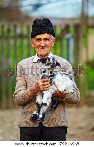Senior farmer holding a baby goat outdoor