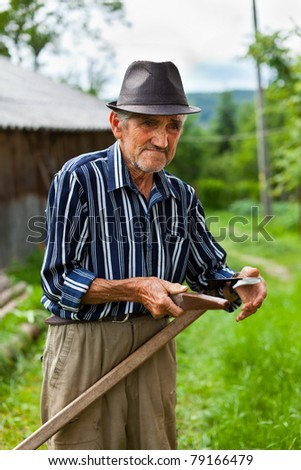 Senior farmer sharpening his scythe to mow the lawn traditionally