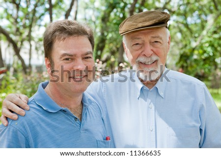 Senior father and his adult son together in the park.  Focus on the older man.