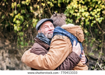 Senior father and his young son on a walk.