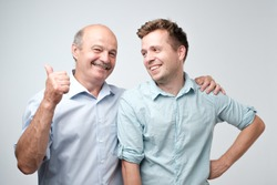 Senior father is proud of his mature son. He is pointing on him saying it is my boy.