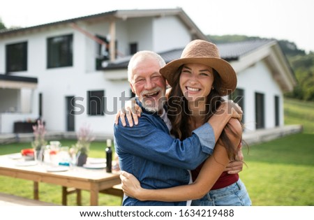 Senior father with daughter outdoors in backyard, looking at camera. Сток-фото ©