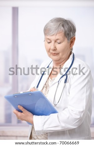 Senior female doctor standing in front of windows, taking notes.?