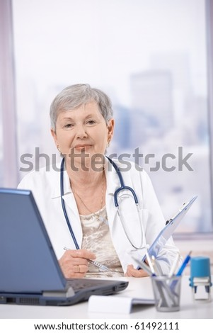 Senior female doctor, working at desk, making notes.? - stock photo
