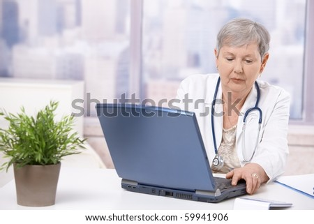 Senior female doctor, working at desk, using laptop computer. Focusing at screen.? - stock photo