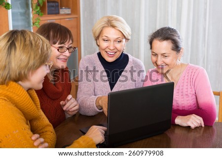 Senior female friends working with notebook using wifi