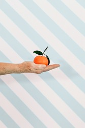 senior female hand holding a tangerine fruit against a blue and white stripes background. third age ealthy food and lifestyle concept