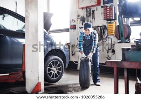 Senior female mechanic repairing a car in a garage. #1028055286