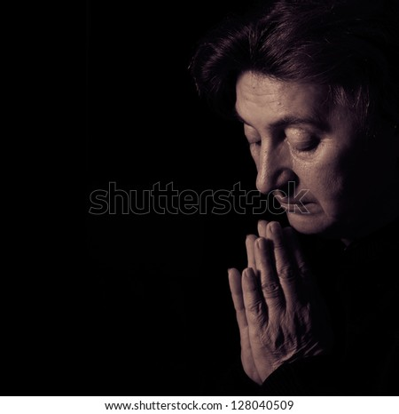 Senior female prayer Low-key studio lighting