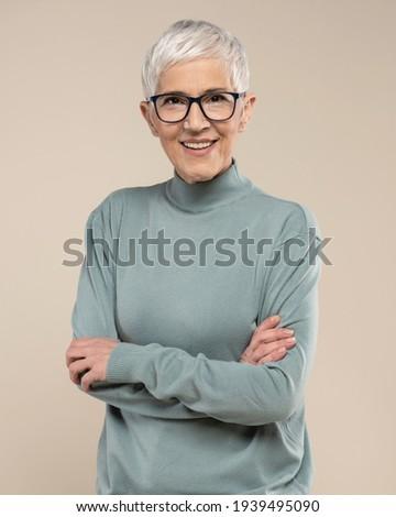 Senior female studio portrait. Short grey hair senior model. Fashion photography in studio. Old female wearing glasses. Confident senior female portrait.