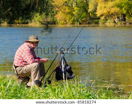 Senior fisherman catches a fish in the river at the bait