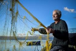 Senior fisherman holding fishing net near the beach. Fisherman hands close up. A fisherman preparing the fishing net