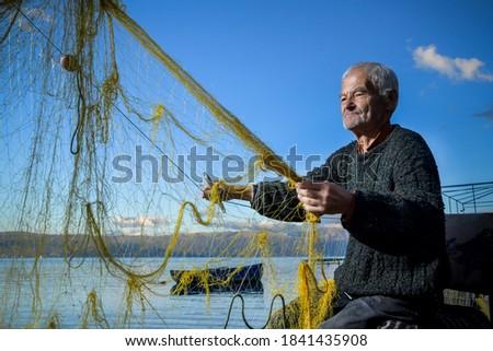 Senior fisherman holding fishing net near the beach. Fisherman hands close up. A fisherman preparing the fishing net ストックフォト ©