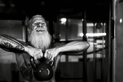 Senior fitness man doing kettle bell exercises inside gym - Fit mature male training in wellness club center - Body building and sport healthy lifestyle concept - Black and white editing