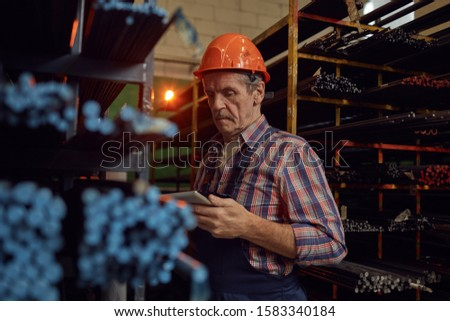 Senior foreman in work helmet standing near the shelves with metal pipes and using digital tablet at warehouse