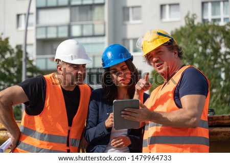 Senior foreman wearing safety vest, helmet and goggles providing instructions to a male and a female colleagues using a digital tablet computer on construction site