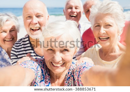 Senior friends taking selfie on the beach