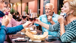 Senior friends toasting wine at restaurant bar wearing opened face mask - New normal lifestyle concept with happy mature people having fun together at garden party - Warm filter with focus on bald man