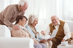 Senior friends watching old photos together on a laptop
