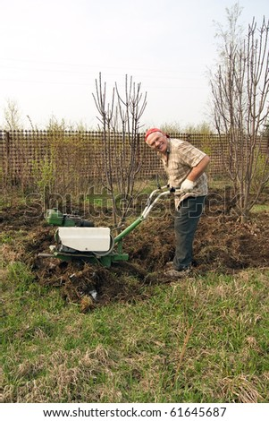 Senior gardener  working in the yard with mini tractor