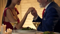 Senior gentleman holding hand of tender young wife, romantic date together