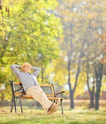 Senior gentleman sitting on wooden bench and relaxing in park, shot with a tilt and shift lens