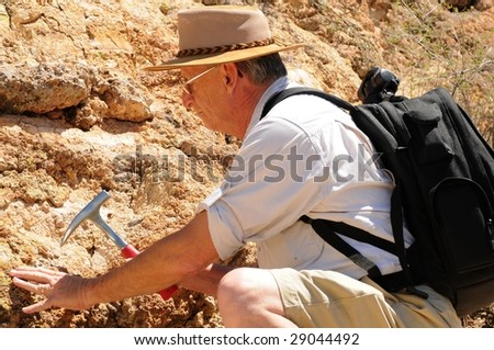 Senior geologist tap a rock formation with a hammer - stock photo