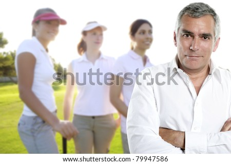 senior golfer man portrait in green course with three women in background [Photo Illustration]