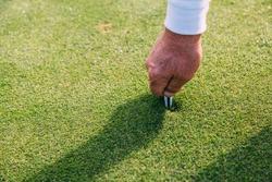 Senior golfer repairing divot on a green grass surface