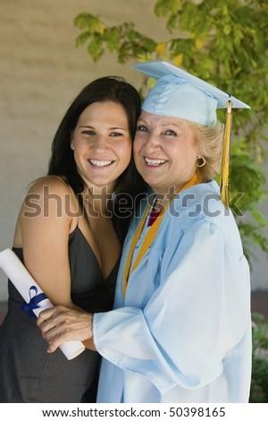 Senior graduate hugging granddaughter outside