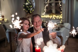 Senior grandfather with small granddaughter indoors at Christmas, having fun with sparklers.