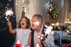 Senior grandfather with small granddaughter indoors at Christmas, sitting at table with sparklers.