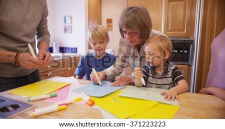 Senior grandma teaching grandchildren to draw. stock photo