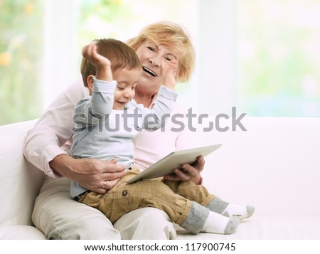 Senior grandmother reading a tale to her grandson from a digital tablet